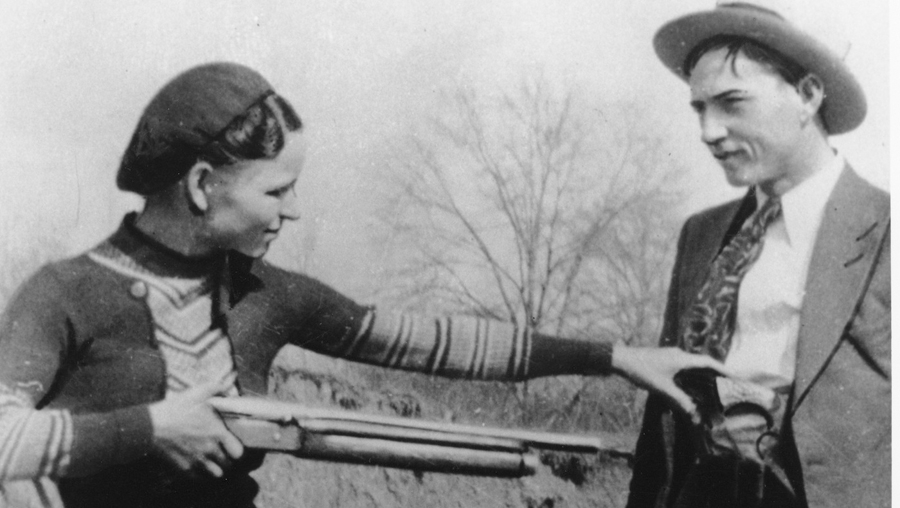 Bonnie playfully points a shotgun at Clyde